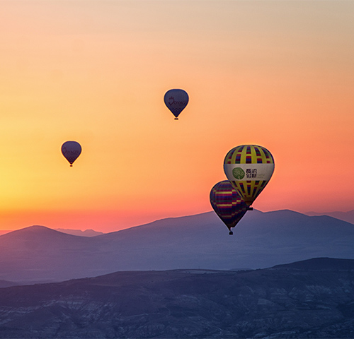 Hot air balloons over the mountains at sunset