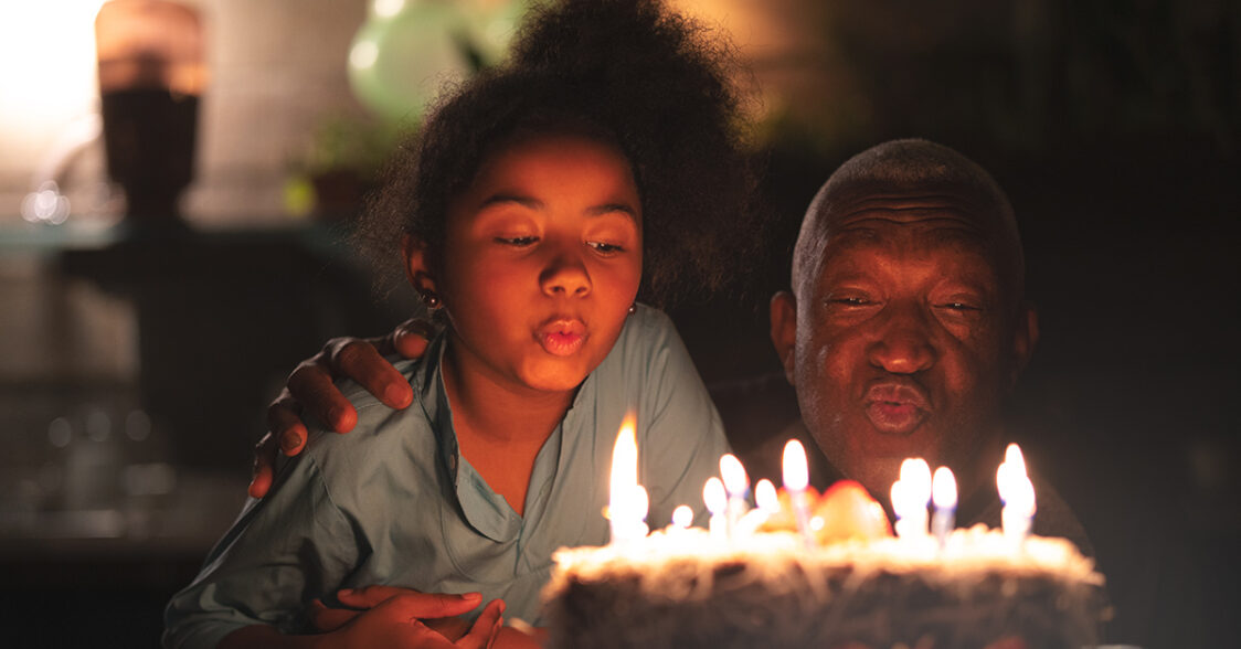 Grandfather and granddaughter blowing out birthday candles
