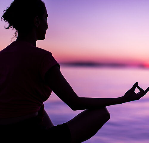 Woman meditating on a beach at sunset