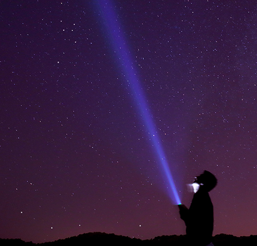 Man shining flashlight into the night sky